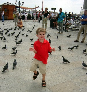 Photo of Aiden in St. Mark's Square with pigeons goes here.