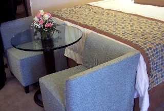 Photo of two-sided chairs and small table in the Penthouse suite goes here.