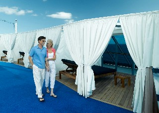 Photo of couple heading for an Oceania Cabana goes here.