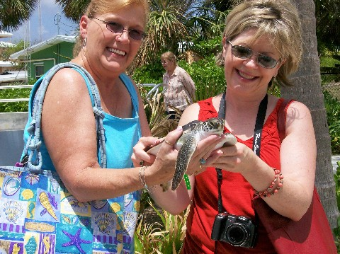 Photo of Nancy (left) and Shelley at the Grand Cayman Turtle Farm goes here.