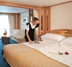 Photo of Seabourn Cruise Line's cabin stewardess making up the bed goes here.