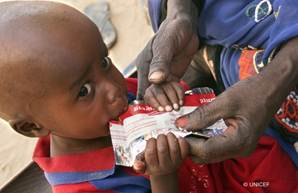 Photo of child eating UNICEF food packet goes here.*