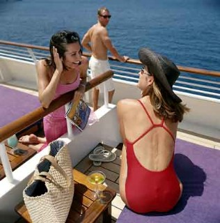 Guests talk over a divider at their SeaDream Balinese Beds on the top deck.