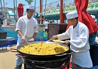 Photo of paella being cooked on an outdoor deck of Norwegian Gem goes here.*